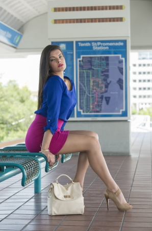 seated: Young woman seated and waiting in a metro station platform