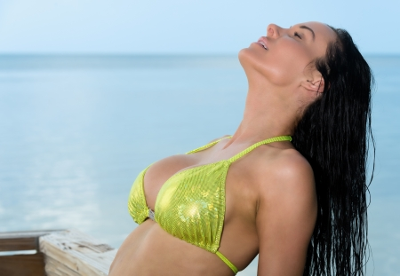 Sensual brunette tanning in a beach photo