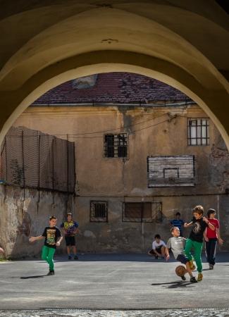 Brasov, Roemenië - 2 oktober 2012 Lokale kinderen voetballen in de straten van Bra ov, Roemenië, met 227.961 mensen die er wonen is de 8e meest bevolkte stad in Roemenië en een populaire toeristische bestemming