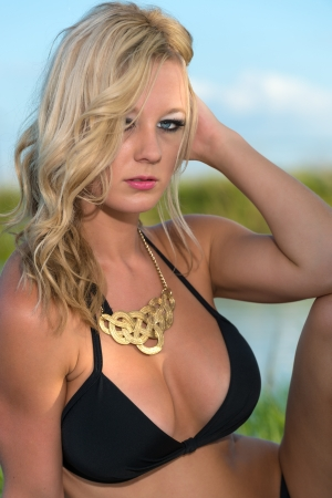 Young and sensual caucasian woman looking at camera in bikini outdoors photo