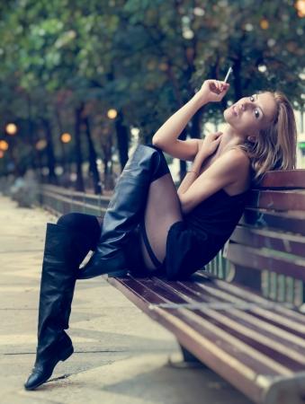 persona fumando: Hermosa mujer sexy rubia en minifalda y botas a largo posando en un banco del parque mirando a la cámara mientras se fuma un cigarrillo