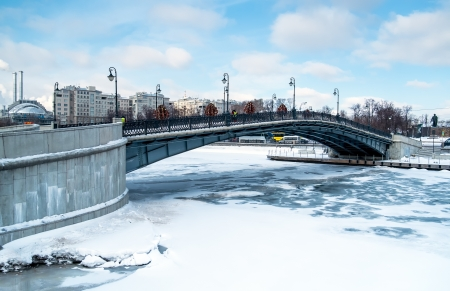 moskva river: View of one of the many bridges crossing the Moskva River in Moscow, during winter time with a frozen river. Stock Photo