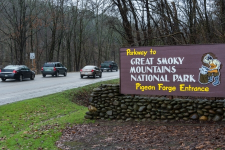 forge: Sign of Pigeon Forge entrance to the Great Smoky Mountains National Park with cars behind