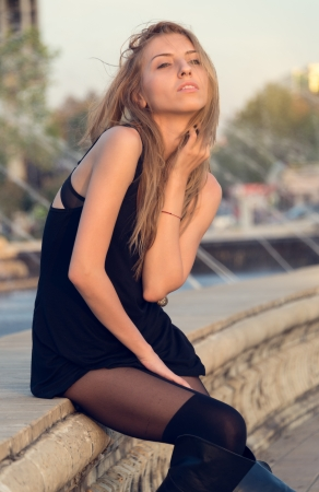 Sexy attractive woman in a short black dress and long boots posing sitting on a wall outdoors with her face raised to the evening sunlight photo