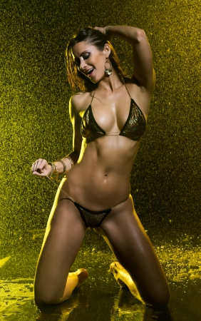 tantalizing: Sensual model in bikini with water behind very playful under yellow light