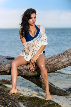 Exotic sexy young woman in a swimsuit and lacy shawl sitting on a branch  photo