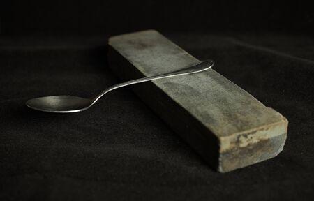 Teaspoon balanced on a long black stone