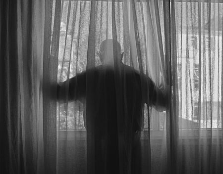 Man looks out the window of a building during confinement due to the COVID-19 coronavirus