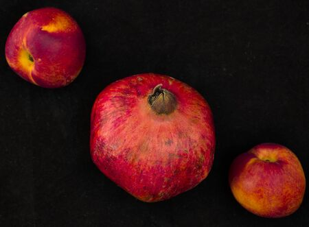 Three pieces of fruit, a pomegranate and two peaches