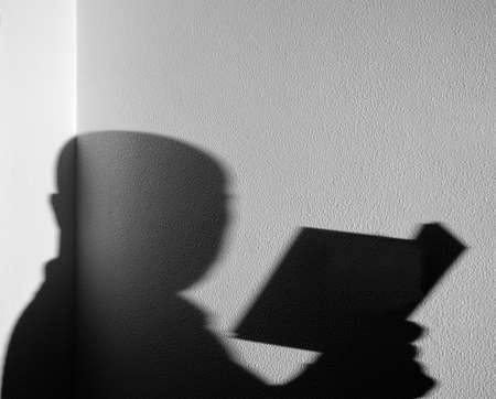 Shadow of a man reading a book on a white wall