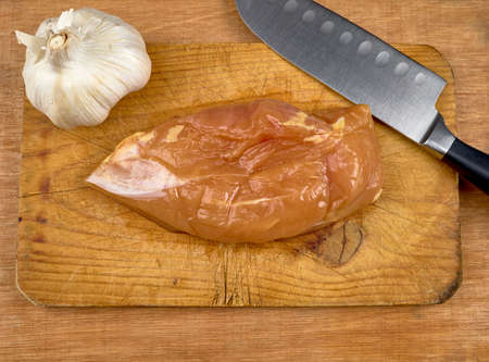 Chicken on a wooden table with a knife and a head of garlic