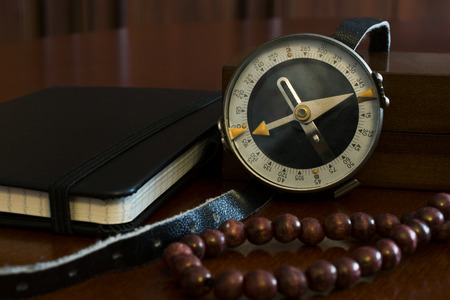 chaplet: Old compass with notebook and chaplet Stock Photo