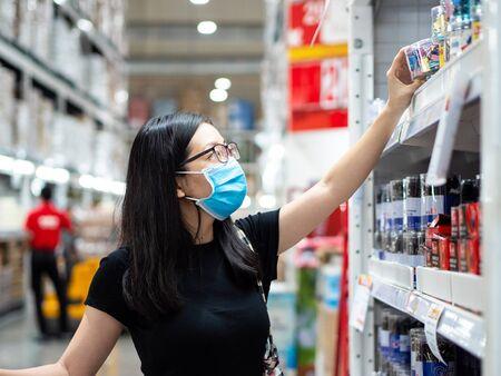 New normal, young asian women wearing mask shopping in the store during coronavirus pandemic crisis.