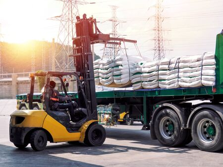 Forklift unloading and loading sugar bags from truck at warehouse dock. Forklift stacking up sugar bag inside warehouse, sugar warehouse operation. Agriculture product storing and logistics for import and export.