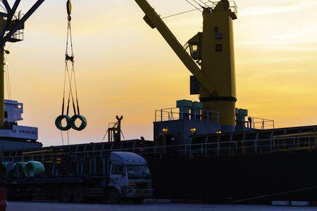 Fil machine en acier déchargeant de la charge du navire sur un camion pour livraison à l'usine. Expédition de produits en acier. Opération de camionnage. Logistique et transport de l'industrie sidérurgique.