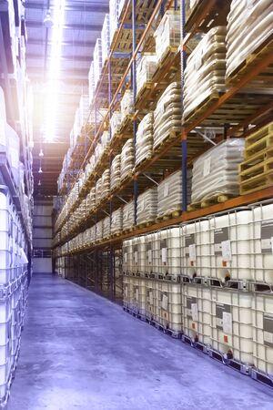 Intérieur d'un grand entrepôt de distribution, palettes et boîtes de fret empilés sur une rangée d'étagères hautes.