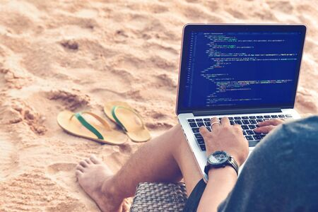 A programmer typing source codes at the beach in a relaxing working environment. Studying, Working, Technology, Freelance Work Concept.