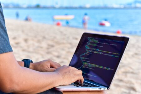 A programmer typing source codes at the beach on a sunny summer day. Studying, Working, Technology, Freelance Work Concept.