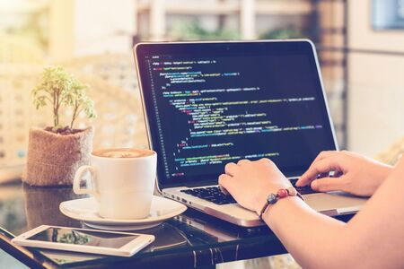 Programmer Typing New Lines of HTML Code. Laptop and Hand Closeup. Working Time. Web Design Business and Web Development Concept. Relaxing Environment. Freelance Work. Programming for all Genders. Stock Photo