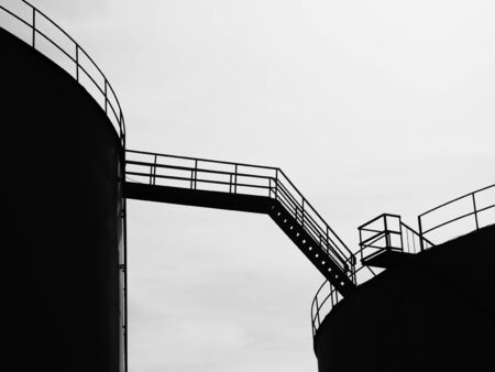 Silhouette of skybridge connecting two  storage tanks at oil and gas tank field.