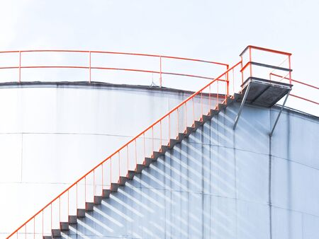Spiral metal stairway climbing up white storage tank at oil and gas tank field.