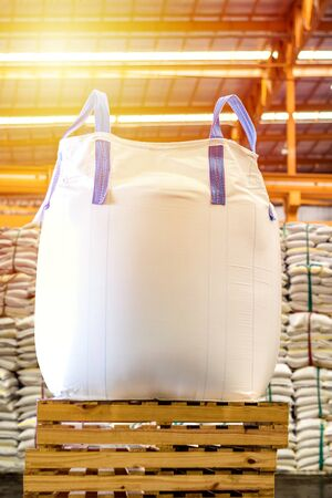Close up of a jumbo bag on wooden pallet with background of bulk sugar bags. Banque d'images