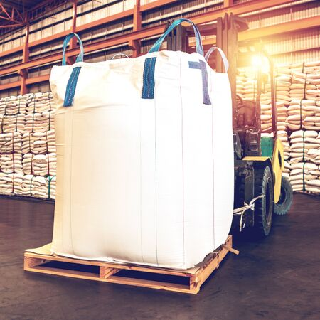 Forklift handling jumbo sugar bag for stuffing into container for export. Distribution, Logistics Import Export, Warehouse operation, Trading, Shipment, Delivery concept.