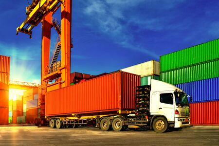 Container handling. Container truck picking up container at yard. Port logistics, container yard operation.