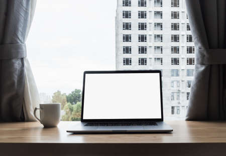 Close up back view of laptop at home near the window with white blank screen for mockup display device in concept of lifestyle work at home with digital technology in millennial.