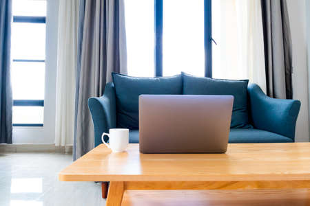 Laptop on wooden table with sofa in cozy room, set up for work from home workstation/online learning.