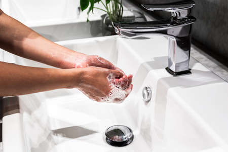 Young asian women washing hand with soap in faucet. New normal, coronavirus prevention.