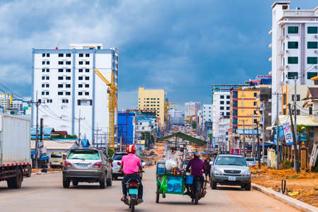 Sihanoukville, Cambodia- July 06, 2020: Traffic on city road under construction during coronavirus pandemic. High rise building under development alongside the road. Éditoriale