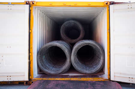 Coils of steel wire rod stuffed inside container. Container open for unloading steel wire rod. Banque d'images