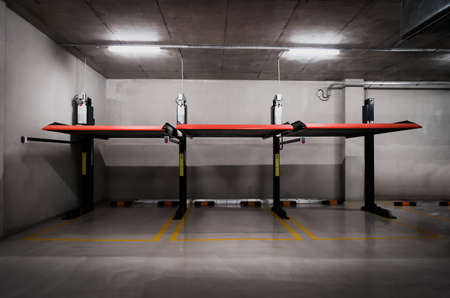 Elevated car parking equipment at office building basement. Car parking space.