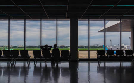 Silhouette of couple sitting at airport terminal waiting for flight.
