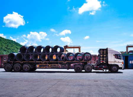 Truck receive steel wire rod from warehouse container unstuffing area. Coils of steel wire rod on truck trailer at industrial zone.