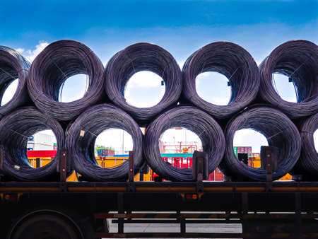 Coils of steel wire rod on truck trailer at industrial zone. Truck receive steel wire rod from warehouse container unstuffing area. Banque d'images