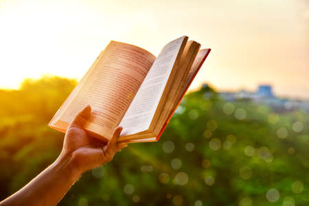 Close-up of man's hands holding a book by the window for reading against sunset with beautiful nature background. warm tone and soft focus. Banque d'images