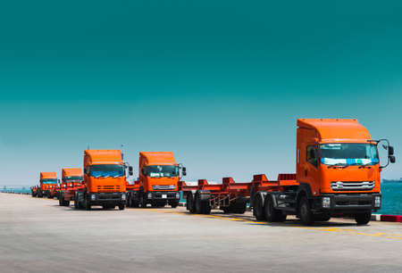 Fleet of trucks and trailer awaiting to pick container on jetty harbour. Container transportation and logistics, trucking and delivery. Banque d'images