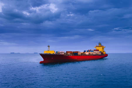 A large red container ship in the open sea with dark clouds background. Shipping, Import, Export, and Logistics concept.