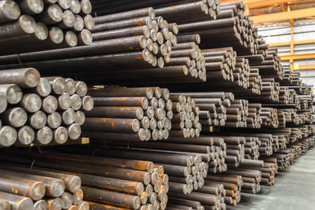 Bundles of steel round bar stack in layer inside large distribution warehouse. Steel warehouse logistics operations. Banque d'images
