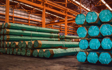Packs of steel tube stack in layers inside storage area of large distribution warehouse. Steel warehouse logistics operations. Banque d'images