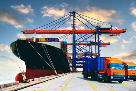 A fleet of heavy-duty trucks receives cargo containers from a huge ship under a quay crane. Container logistic import export and transport industry background.