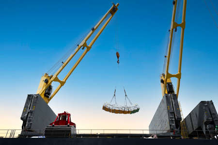 Ship crane lift jumbo sling of sugar bags load into ship hold. Bag cargo loading to ship for export. Banque d'images