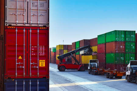 Container yard operation activity, reach stacker load container onto trailers. Container terminal, port operation, and logistics.
