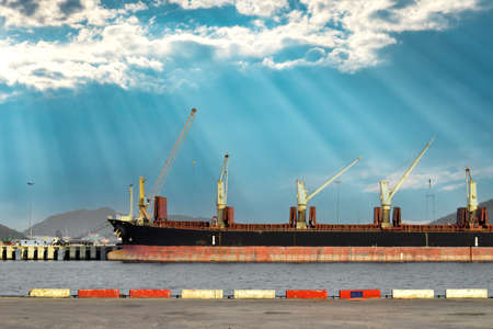 Side view of a huge bulk cargo ship docking at harbor discharging steel cargo with a beautiful sky background.