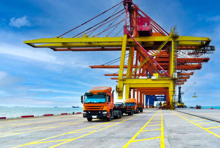 Front view of truck fleet line up under quay crane leaving the port after discharging containers with sea and blue sky background.