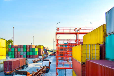 High angle view of container yard operation, heavy equipment reach stacking loading up container to truck and trailer. Container shipping, logistics, transportation, and supply chain.