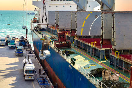 High angle view of huge cargo ship discharge steel at port terminal. Ship crane lift steel coil put down on truck for delivery. Banque d'images