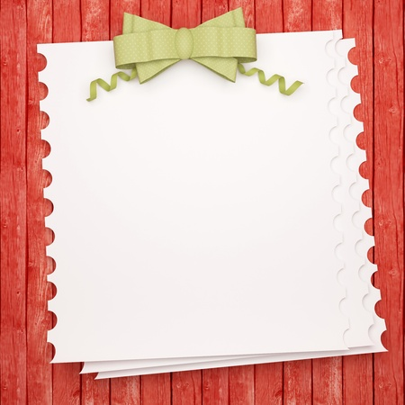 your text: Vintage holiday paper background with green bow, white invitation blank in front of red wooden wall for insert your text (design).